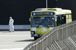 A bus drives near the quarantined Diamond Princess cruise ship anchored at a port in Yokohama, near Tokyo, Wednesday, Feb. 19, 2020. The cruise ship begins letting passengers off the boat on Wednesday after it's been in quarantined for 14 days. (AP Photo/Eugene Hoshiko)