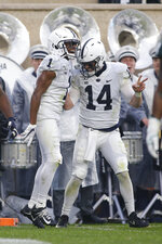 Penn State receiver KJ Hamler, left, and quarterback Sean Clifford (14) celebrate Hamler's touchdown reception against Michigan State during the second quarter of an NCAA college football game, Saturday, Oct. 26, 2019, in East Lansing, Mich. (AP Photo/Al Goldis)