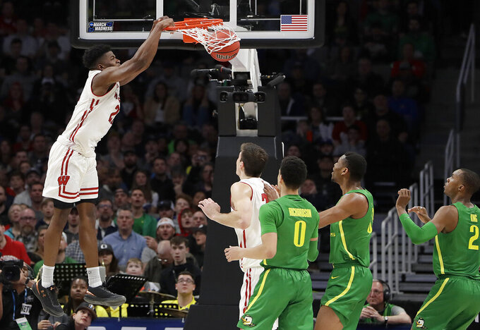 Wisconsin guard Khalil Iverson, left, dunks against Oregon during the first half of a first-round game in the NCAA men's college basketball tournament Friday, March 22, 2019, in San Jose, Calif. (AP Photo/Chris Carlson)