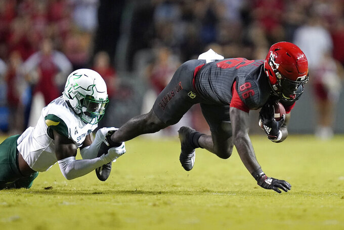 South Florida defensive back TJ Robinson (2) tackles North Carolina State wide receiver Emeka Emezie (86) during the first half of an NCAA college football game in Raleigh, N.C., Thursday, Sept. 2, 2021. (AP Photo/Gerry Broome)