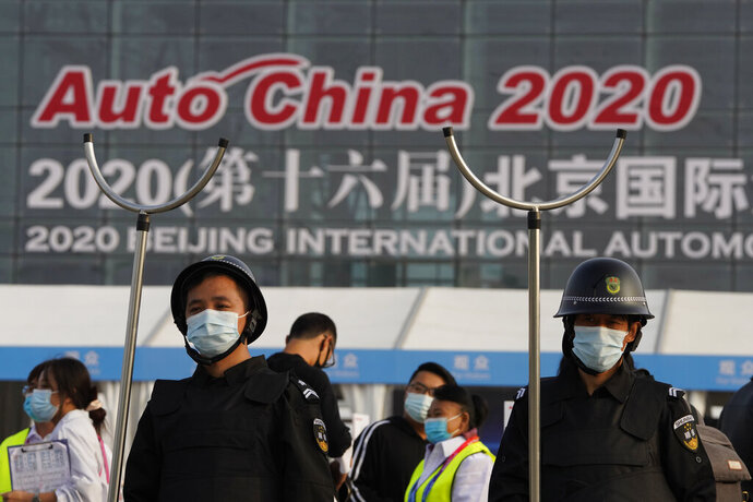 Security guards wearing masks and armed with restrainers stand guard at the entrance to the Auto China 2020 show in Beijing, China on Saturday, Sept. 26, 2020. The auto show, the first major in-person sales event for any industry since the coronavirus pandemic began, opens Saturday in a sign the ruling Communist Party is confident China has contained the disease. Still, automakers face intensive anti-virus controls including quarantines for visitors from abroad and curbs on crowd sizes at an event that usually is packed shoulder-to-shoulder with spectators. (AP Photo/Ng Han Guan)