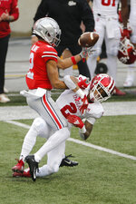 Ohio State receiver Chris Olave, left, bobbles the ball as Indiana defensive back Reese Taylor defends during the first half of an NCAA college football game Saturday, Nov. 21, 2020, in Columbus, Ohio. (AP Photo/Jay LaPrete)