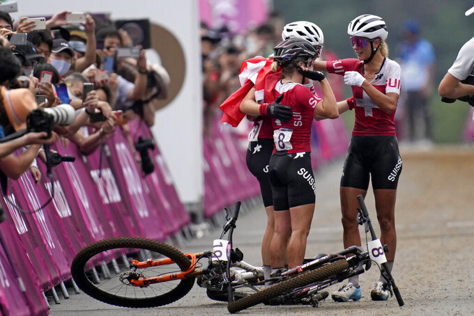 Jolanda Neff of Switzerland, right, embraces teammates Sina Frei (8) who won silver, and Linda Indergand, who won bronze, for a sweep of the podium for Switzerland, at the finish line the women's cross-country mountain bike competition at the 2020 Summer Olympics, Tuesday, July 27, 2021, in Izu, Japan. (AP Photo/Christophe Ena)