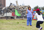 Jamila Alvarez takes a photo of Sarah Cruz in front of the remains of the Affiliated Computer Services building or the Leaning to Tower of Dallas on Monday, March 2, 2020 in Dallas. The Leaning Tower of Dallas, the nearly iconic remnant of a high-rise building implosion gone awry, finally collapsed in a cloud of dust Monday after two weeks of being whacked with a headache ball. (Juan Figueroa/The Dallas Morning News via AP)