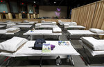 FILE - In this April 22, 2021 file photo, a sleeping area set up inside exhibit hall B of the Long Beach Convention Center in Long Beach, Calif., where migrant children found at the U.S.-Mexico border without a parent will be temporarily housed. The Biden administration is holding tens of thousands of asylum-seeking children in an opaque network of some 200 facilities that The Associated Press has now learned spans two dozen states and includes five shelters with more than 1,000 children packed inside. (Brittany Murray/The Orange County Register via AP, Pool, File)