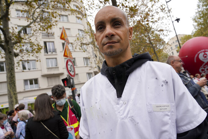 Rachid Ouchem, a medical worker from the Plaisir Hospital, attends a protest gathering outside the Health Ministry in Paris, Tuesday, Sept. 14, 2021 against a law requiring them to get vaccinated by Wednesday or risk suspension from their jobs. The law is aimed at protecting patients from new surges of COVID-19. Most of the French population is vaccinated but a vocal minority are against the vaccine mandate. (AP Photo/Francois Mori)