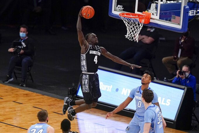 Georgetown's Chudier Bile (4) dunks the ball in front of Creighton's Ryan Kalkbrenner (32) and Antwann Jones (0) during the second half of an NCAA college basketball game in the championship of the Big East Conference tournament Saturday, March 13, 2021, in New York. (AP Photo/Frank Franklin II)