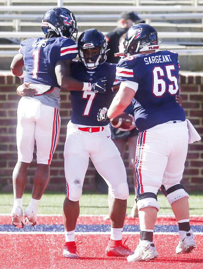Liberty quarterback Malik Willis (7) celebrates his touchdown with his teammates during the first half of an NCAA football game on Saturday, Nov. 14, 2020, in Lynchburg, Va. (AP Photo/Shaban Athuman)