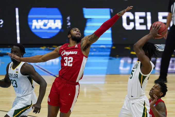 Houston forward Reggie Chaney (32) tries to block a shot by Baylor guard Davion Mitchell (45) during the first half of a men's Final Four NCAA college basketball tournament semifinal game, Saturday, April 3, 2021, at Lucas Oil Stadium in Indianapolis. (AP Photo/Michael Conroy)