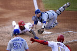 Washington Nationals' Eric Thames, left, slides past Toronto Blue Jays catcher Danny Jansen, right, while scoring on a double by Kurt Suzuki during the fourth inning of a baseball game Monday, July 27, 2020, in Washington. Watching are Nationals' Victor Robles (16) and Blue Jays starting pitcher Trent Thornton (57). (AP Photo/Nick Wass)