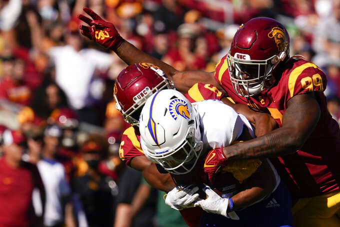 San Jose State wide receiver Isaiah Hamilton, center, is tackled by Southern California cornerback Isaac Taylor-Stuart (6) and linebacker Drake Jackson (99) during the second half of an NCAA college football game Saturday, Sept. 4, 2021, in Los Angeles. (AP Photo/Ashley Landis)