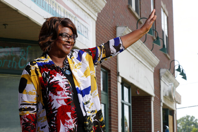 Mayor-elect Ella Jones waves to a supporter passing by while posing for a photo Wednesday, June 3, 2020, in Ferguson, Mo. Jones, currently a city council member who was elected mayor on Tuesday, will become the first black and first woman mayor of the city thrust into the national spotlight after the death of Michael Brown in 2014. (AP Photo/Jeff Roberson)