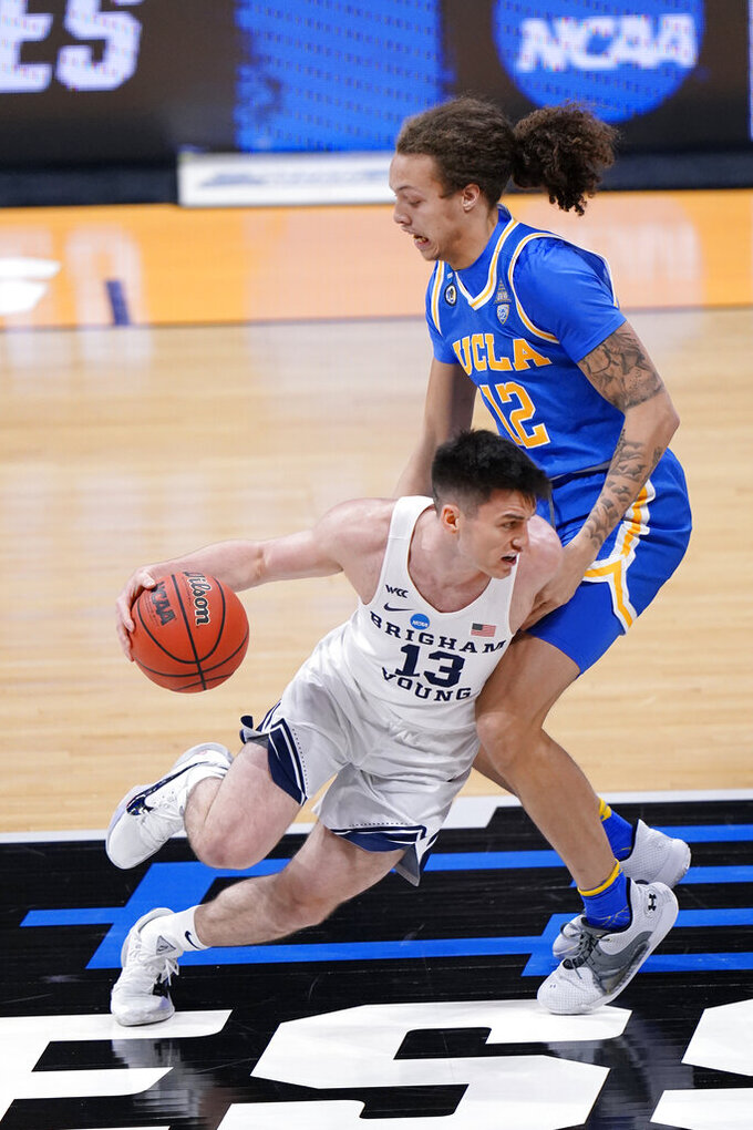 BYU guard Alex Barcello (13) drives past UCLA forward Mac Etienne (12) during the first half of a first-round game in the NCAA college basketball tournament at Hinkle Fieldhouse in Indianapolis, Saturday, March 20, 2021. (AP Photo/AJ Mast)
