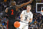 Utah State guard Sam Merrill (5) passes the ball as San Diego State guard Adam Seiko (2) defends during the first half of an NCAA college basketball game Saturday, Jan. 4, 2020, in Logan, Utah. (AP Photo/Eli Lucero)