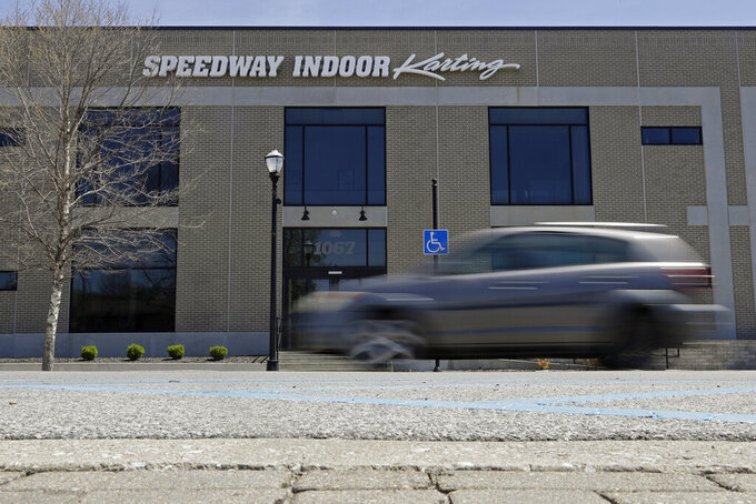 A car drives past Speedway Indoor Karting, Tuesday, April 21, 2020, in Indianapolis. Former IndyCar driver Sarah Fisher found the perfect spot for her new venture, Speedway Indoor Karting, just a short stroll from Indianapolis Motor Speedway which is closed due to the coronavirus pandemic. (AP Photo/Darron Cummings)