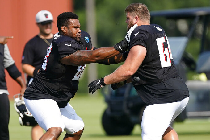 Atlanta Falcons offensive guards Josh Andrews (68), left, and Ryan Neuzil (64) run a drill during the team's NFL training camp football practice Monday, Aug. 9, 2021, in Flowery Branch, Ga. (AP Photo/John Bazemore)