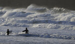 Bodysurfers enter the sea on a beach in St Ives, south west England, Sunday, Feb. 16, 2020. Storm Dennis roared across Britain on Sunday, lashing towns and cities with high winds and dumping so much rain that authorities urged residents to protect themselves from