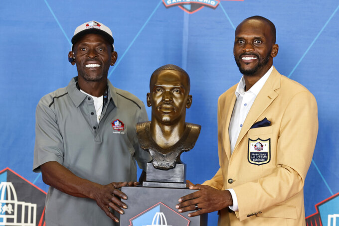 Isaac Bruce, right, a member of the Pro Football Hall of Fame Centennial Class, poses with his presenter, Sam Bruce, during the induction ceremony at the Pro Football Hall of Fame, Saturday, Aug. 7, 2021, in Canton, Ohio. (AP Photo/Ron Schwane, Pool)