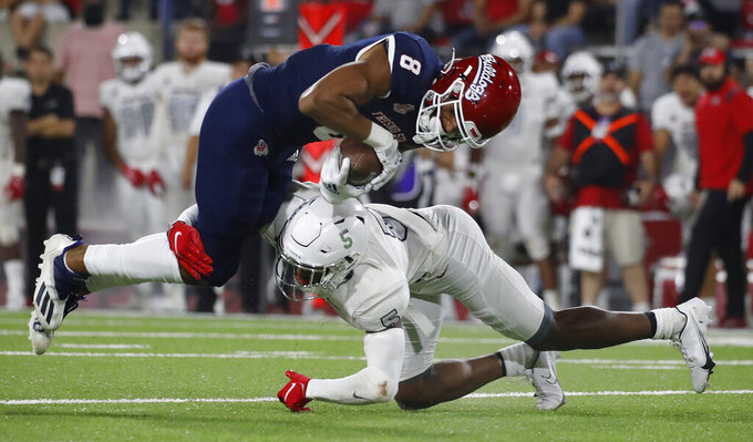 Fresno State wide receiver Ty Jones goes over UNLV defensive back Phillip Hill during the second half of an NCAA college football game in Fresno, Calif., Friday, Sept. 24, 2021. (AP Photo/Gary Kazanjian)