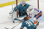 New York Islanders defenseman Nick Leddy (2) tries to control the puck between San Jose Sharks goaltender Martin Jones (31) and center Logan Couture (39) during the third period of an NHL hockey game in San Jose, Calif., Saturday, Nov. 23, 2019. The Sharks won 2-1 in overtime. (AP Photo/Jeff Chiu)