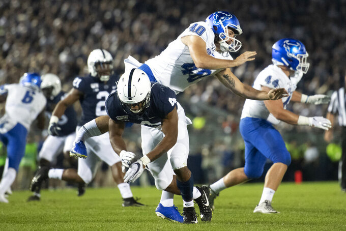 Penn State running back Journey Brown (4) tips a punt by Buffalo punter Evan Finegan (40) during the third quarter of an NCAA college football game in State College, Pa., Saturday, Sept. 7, 2019. Finegan was injured on the play and carted off the field. (AP Photo/Barry Reeger)