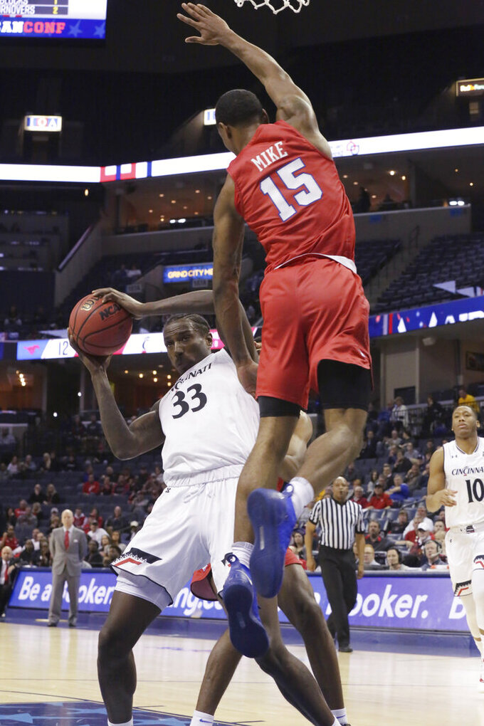 SMU's Isiaha Mike leaps to defend on a shot attempt by Cincinnati's Nyster Brooks during the first half of an NCAA college basketball game at the American Athletic Conference men's tournament Friday, March 15, 2019, in Memphis, Tenn. (AP Photo/Troy Glasgow)
