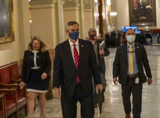 Georgia Secretary of State Brad Raffensperger, center, walks with members of his staff as they make their way to a press conference at the Georgia State Capitol building in Atlanta, Wednesday, Dec. 2, 2020. (Alyssa Pointer/Atlanta Journal-Constitution via AP)