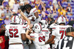 South Carolina's Cam Smith (9) jumps on top of teammates celebrating their win over East Carolina at an NCAA college football game in Greenville, N.C., Saturday, Sept. 11, 2021. (AP Photo/Karl B DeBlaker)