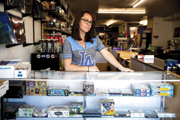 Jessie Studle, owner of Dungeons and Dugouts, poses at the counter of her store in Gillette, Wyo., on Friday, June 4, 2020. A boom in trading cards brings in new customers but higher prices can keep others from taking part in the hobby, Studle said. (Mike Moore/Gillette News Record via AP)