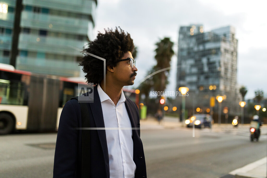 Spain, Barcelona, businessman standing at a street in the city at dusk