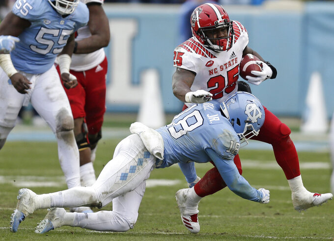 North Carolina State's Reggie Gallaspy II (25) runs while North Carolina's Corey Bell Jr. (18) tackles during the first half of an NCAA college football game in Chapel Hill, N.C., Saturday, Nov. 24, 2018. (AP Photo/Gerry Broome)