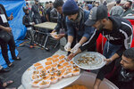 In this photo taken Sunday, Dec. 8, 2019, a volunteers serve free meals of the popular dish of Fish and Rice to protesters, in the center of Baghdad, Iraq. In Baghdad's Tahrir Square, there are the anti-government protesters demonstrating for a better future for Iraq, and there are the volunteers who feed them. From stuffed lamb and fish, to the giant pots of soups and rice to the plates of lentils and beans, there is no shortage of food to go around. Volunteers from the capital and southern provinces cook traditional dishes that reflect the country's rich cuisine and bring protesters together.   (AP Photo/Nasser Nasser)