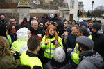 FILE - In this Jan.15, 2019 file photo, Ingrid Levavasseur, center, one of the leading figures of France's Yellow Vests protests, talks to residents and protestors as she waits for French President Emmanuel Macron's visit in Bourgtheroulde, Normandy. The blaze at Notre Dame has sent a shockwave through France, but Levavasseur believes that the image of unbroken national unity felt in the aftermath of the fire is politically exploited by Macron. (AP Photo/Francois Mori, File)