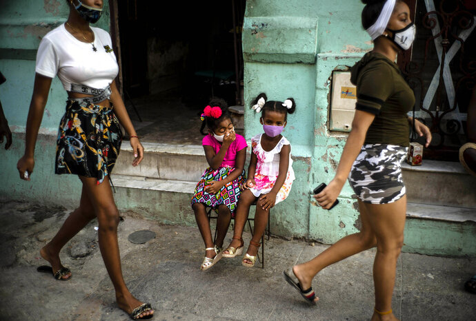 Wearing a mask as a precaution against the spread of the new coronavirus Angelica Victoria, center left, and Thalia Oneida, wait for their parents sitting on a chair in Havana, Cuba, Monday, Oct. 12, 2020. Cuba relaxed coronavirus restrictions Monday in hopes of boosting its economy, allowing shops and government offices to reopen and welcoming locals and tourists at airports across the island except in Havana. (AP Photo/Ramon Espinosa)