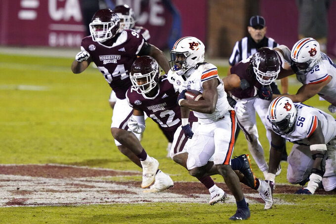 Auburn running back Tank Bigsby (4) sprints past Mississippi State safety Shawn Preston Jr. (12) and other defenders on his way to a short gain during the second half of an NCAA college football game Saturday, Dec. 12, 2020, in Starkville, Miss. (AP Photo/Rogelio V. Solis)