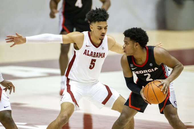 Alabama guard Jaden Shackelford (5) defends against Georgia guard Sahvir Wheeler (2) during the second half of an NCAA college basketball game on Saturday, Feb. 13, 2021, in Tuscaloosa, Ala. (AP Photo/Vasha Hunt)