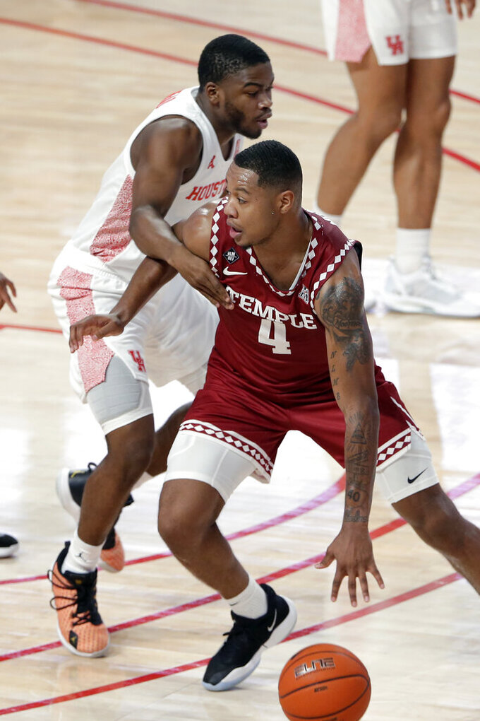 Temple forward J.P. Moorman II (4) is fouled as he drives around Houston guard Jamal Shead (1) during the first half of an NCAA college basketball game Tuesday, Dec. 22, 2020, in Houston. (AP Photo/Michael Wyke)