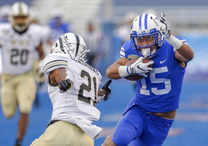BYU wide receiver Aleva Hifo (15) avoids the reach of Western Michigan defensive back Stefan Claiborne (21) on a 70-yard touchdown reception in the second half of the Famous Idaho Potato Bowl NCAA college football game, Friday, Dec. 21, 2018, in Boise, Idaho. (AP Photo/Steve Conner)