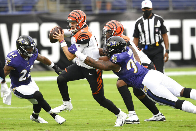 Cincinnati Bengals quarterback Joe Burrow, center, scrambles for yardage against Baltimore Ravens cornerback Jimmy Smith (22) and outside linebacker Matt Judon (99) during the first half of an NFL football game, Sunday, Oct. 11, 2020, in Baltimore. (AP Photo/Nick Wass)