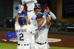 Texas Rangers' Jeff Mathis (2), Anderson Tejeda, right, and Ronald Guzman, rear, celebrate Mathis' three-run home run that scored them in the seventh inning of a baseball game against the Houston Astros in Arlington, Texas, Saturday, Sept. 26, 2020. (AP Photo/Tony Gutierrez)