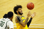 Michigan forward Isaiah Livers attempts to control the ball during the first half of an NCAA college basketball game against Michigan State, Sunday, March 7, 2021, in East Lansing, Mich. (AP Photo/Carlos Osorio)