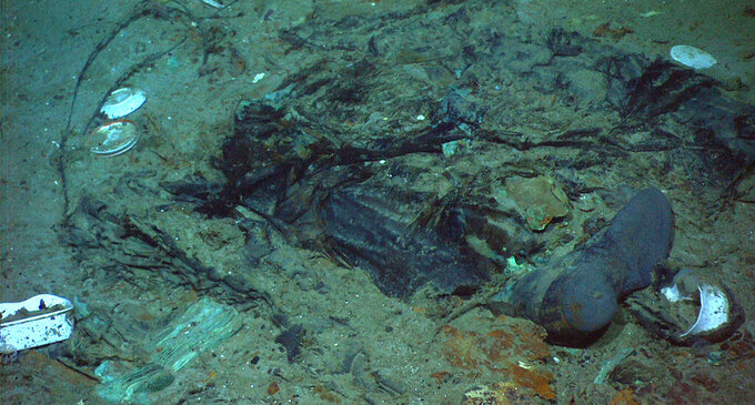 FILE - This 2004 photo provided by the Institute for Exploration, Center for Archaeological Oceanography/University of Rhode Island/NOAA Office of Ocean Exploration, shows the remains of a coat and boots in the mud on the sea bed near the Titanic's stern. OceanGate Expeditions, an undersea exploration company, plans to dive to the sunken Titanic to begin what's expected to be an annual chronicling of the shipwreck's deterioration. The 109-year-old wreck is being battered by deep-sea currents and metal-eating bacteria. The first dive could be as early as this week. (Institute for Exploration, Center for Archaeological Oceanography/University of Rhode Island/NOAA Office of Ocean Exploration)