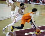 Oklahoma State guard Cade Cunningham (2) goes against Oklahoma guard Elijah Harkless (24) during the second half of an NCAA college basketball game, Saturday, Feb. 27, 2021, in Norman, Okla. (AP Photo/Garett Fisbeck)