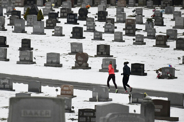 FILE - In this Friday, Jan. 24, 2020 file photo, two joggers run through Grandview Cemetery in Johnstown, Pa. Data released on Thursday, Jan. 30, 2020 shows that U.S. life expectancy has improved for the first time in four years, thanks to a sharp decline in the cancer death rate and to a drop in fatal drug overdoses. (Todd Berkey/The Tribune-Democrat via AP)