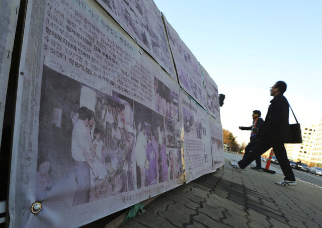 In this April 2, 2019, file photo, people walk past a photo of guards unloading children from a truck at the Brothers Home in Busan as it is displayed in front of National Assembly in Seoul, South Korea. South Korea's Supreme Court said Friday, April 17, 2020, it will re-open a case related to the enslavement and abuse of thousands of people at a vagrants' facility in the 1970s and 1980s, more than three decades after its owner was acquitted of serious charges. (AP Photo/Ahn Young-joon, File)