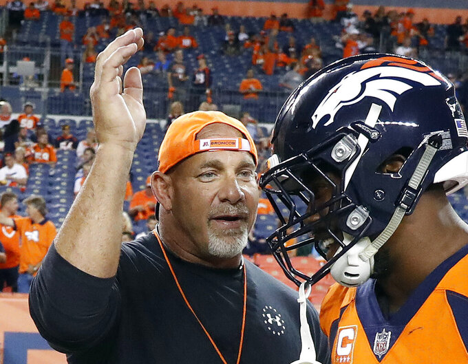 FILE - In this Sept. 11, 2017, file photo, professional wrestler Bill Goldberg, left, greets Denver Broncos outside linebacker Von Miller prior to an NFL football game against the Los Angeles Chargers in Denver. The 54-year-old Goldberg returns for his second match of the year when he challenges Bobby Lashley for the WWE title Saturday night, Aug. 21, 2021, at SummerSlam at Allegiant Stadium. (AP Photo/Jack Dempsey, File)