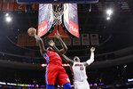 Philadelphia 76ers' Joel Embiid, left, goes up to shoot against Miami Heat's Bam Adebayo during the first half of an NBA basketball game, Saturday, Nov. 23, 2019, in Philadelphia. (AP Photo/Matt Slocum)