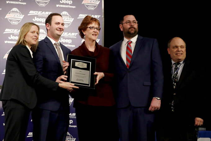 Anne O'Connell, center, widow of former Associated Press college basketball writer Jim O'Connell, stands with their sons, Andrew O'Connell, second from left, and James O'Connell, second from right, after they received a media award in his honor from the Big East Conference, before the Big East men's college basketball tournament Wednesday, March 13, 2019, in New York. Also seen are Big East commissioner Val Ackerman, left, and associated commissioner John Paquette, right. (AP Photo/Julio Cortez)
