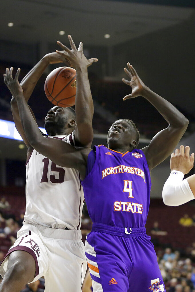 Texas A&M forward Jonathan Aku (15) fights for a rebound against Northwestern State forward Chudier Bile (4) during the first half of an NCAA college basketball game Wednesday, Nov. 6, 2019, in College Station, Texas. (AP Photo/Sam Craft)