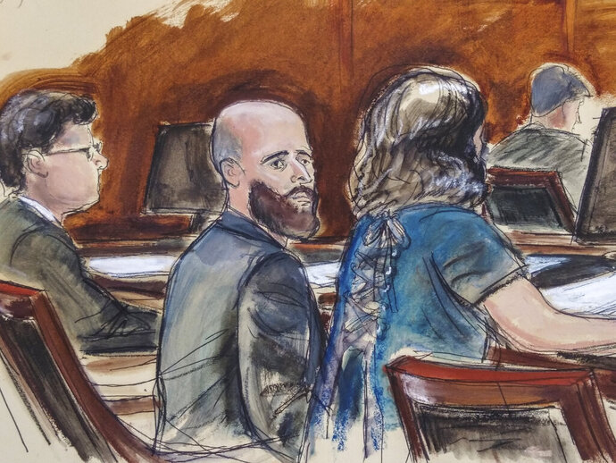"""In this Wednesday March 4, 2020 courtroom sketch Joshua Schulte, center, is seated at the defense table flanked by his attorneys during jury deliberations in New York. Joshua Schulte, a former CIA software engineer charged with leaking government secrets to WikiLeaks says it's cruel and unusual punishment that he's awaiting trial in solitary confinement, housed in a vermin-infested cell of a jail unit where inmates are treated like """"caged animals."""